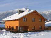 Celkový pohľad na objekt a zasnežené hory v zime..